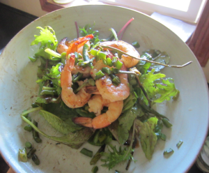 A salad with Grilled Shrimp, EverGood garlic scapes, and baby greens.